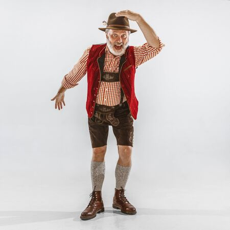 Portrait of Oktoberfest senior man in hat, wearing the traditional Bavarian clothes. Male full-length shot at studio on white background. The celebration, holidays, festival concept. Inviting, calling.