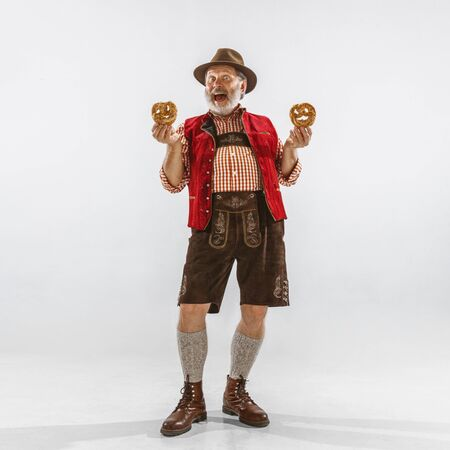 Portrait of Oktoberfest senior man in hat, wearing the traditional Bavarian clothes. Male full-length shot at studio on white background. The celebration, holidays, festival concept. Eating puffs.