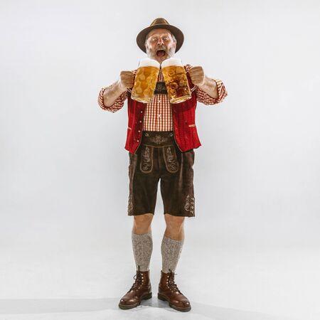 Porträt des älteren Mannes des Oktoberfests im Hut, der die traditionelle bayerische Kleidung trägt. Männlicher Schuss in voller Länge im Studio auf weißem Hintergrund. Die Feier, Feiertage, Festivalkonzept. Lädt auf Bier ein.