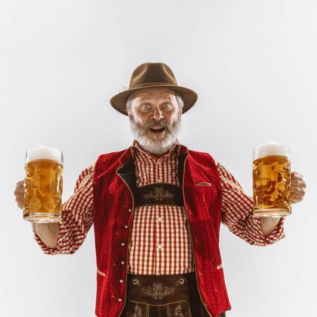 Portrait of Oktoberfest senior man in hat, wearing the traditional Bavarian clothes. Male full-length shot at studio on white background. The celebration, holidays, festival concept. Invites on beer.