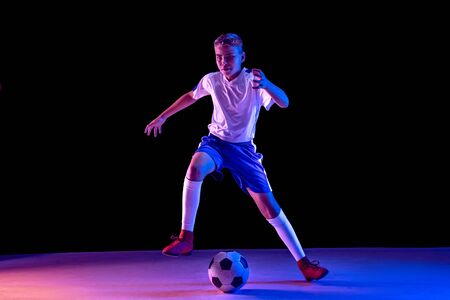 Young boy as a soccer or football player in sportwear making a feint or a kick with the ball for a goal on dark studio background. Fit playing boy in action, movement, motion at game. Purple neon light,