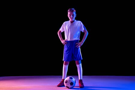 Young boy as a soccer or football player in sportwear standing with the ball on dark studio background. Fit playing boy in action, movement, motion at game. Purple neon light. Look confident.
