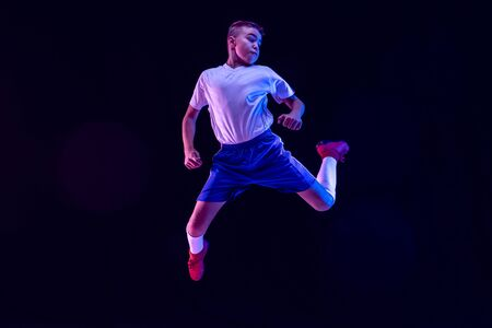 Young boy as a soccer or football player in sportwear making a feint or a kick with the ball for a goal on dark studio background. Fit playing boy in action, movement, motion at game. Purple neon light. Stockfoto