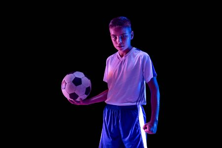 Young boy as a soccer or football player in sportwear standing with the ball on dark studio background. Fit playing boy in action, movement, motion at game. Confident. Purple neon light. Stockfoto