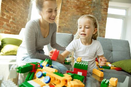 Female caucasian teacher and little girl, or mom and daughter. Homeschooling. Sitting on the sofa with plastic constructor, learning, talking and having fun. Education, school, studying concept.
