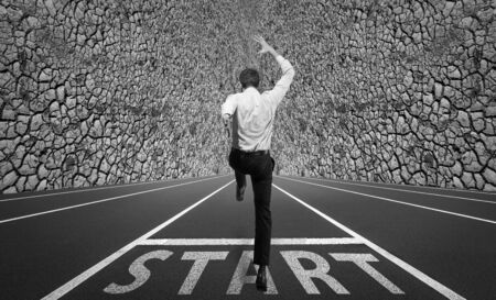 Businessman jumping on a starting grid with the wall on the background. Caucasian man, empoyer in suit starting the career like a race. Business, work, occupation, finance concept. Has no chances.