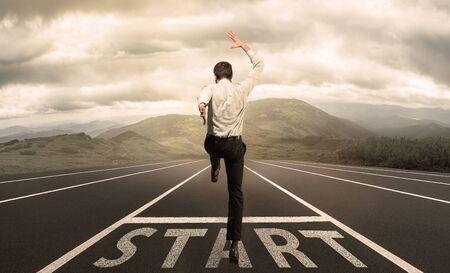 Geschäftsmann springt auf eine Startaufstellung mit der Wiese im Hintergrund. Kaukasischer Mann, Arbeitgeber im Anzug, der die Karriere wie ein Rennen beginnt. Geschäft, Arbeit, Beruf, Finanzkonzept. Neue Träume.