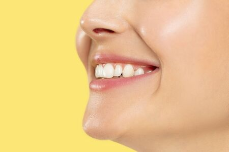 Close up shot of young woman on yellow studio background. Beautiful female model with well-kept skin. Concept of human emotions, facial expression, beauty, healthy lifestyle. Lips, teeth smiling.