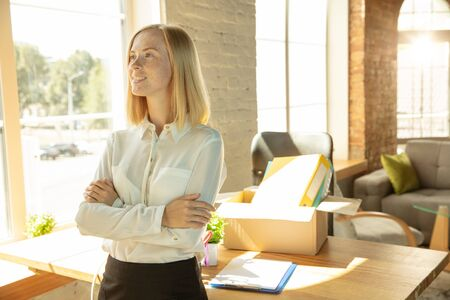 A young businesswoman moving in the office, getting new work place. Young caucasian female office worker looks inspired and confident after promotion. Looks happy. Business, lifestyle, new life concept.