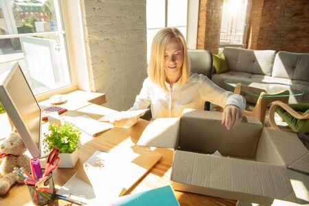 Eine junge Geschäftsfrau, die im Büro umzieht und einen neuen Arbeitsplatz bekommt. Junge kaukasische Büroangestellte stattet neues Kabinett nach der Beförderung aus. Kartons auspacken. Geschäft, Lebensstil, neues Lebenskonzept. Standard-Bild