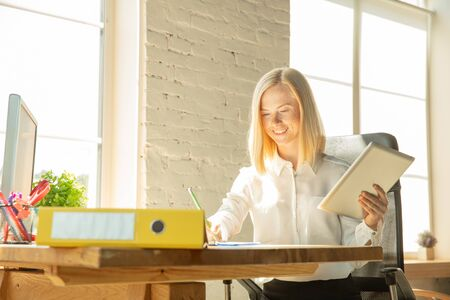 A young businesswoman moving in the office, getting new work place. Young caucasian female office worker equips new cabinet after promotion. Using tablet. Business, lifestyle, new life concept. Stock Photo