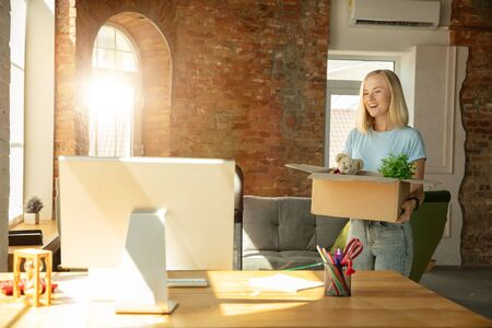 A young businesswoman moving in the office, getting new work place. Young caucasian female office worker equips new cabinet after promotion. Looks happy. Business, lifestyle, new life concept.
