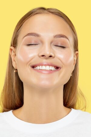 Caucasian young womans close up shot on yellow studio background. Beautiful female model with perfect well-kept skin. Concept of human emotions, facial expression, beauty, healthy lifestyle.