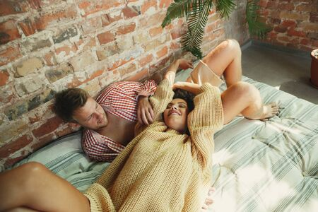 Couple of lovers at home relaxing together. Caucasian man and woman having weekend, looks tender and happy. Concept of relations, family, autumn and winter comfort. Lying and talking, smiling.