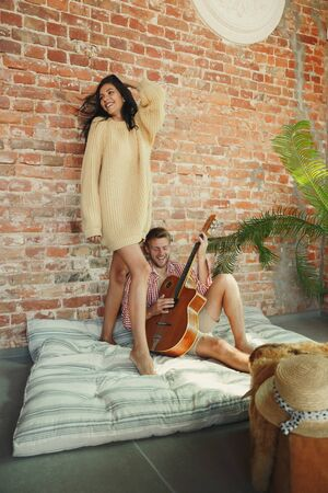 Couple of lovers at home relaxing together. Caucasian man playing guitar while woman dancing. Having weekend, looks tender and happy. Concept of relations, family, autumn and winter comfort.