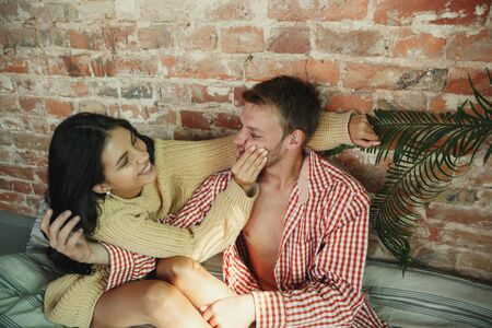 Couple of lovers at home relaxing together. Caucasian man and woman having weekend, looks tender and happy. Concept of relations, family, autumn and winter comfort. Hugging and laughting. 写真素材