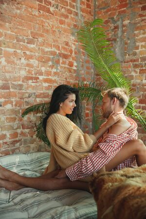 Couple of lovers at home relaxing together. Caucasian man and woman having weekend, looks tender and happy. Concept of relations, family, autumn and winter comfort. Pure emotions.