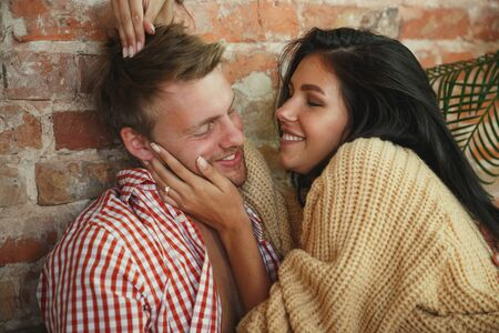 Pure happiness. Couple of lovers at home relaxing together. Caucasian man and woman having weekend, looks tender and happy. Concept of relations, family, autumn and winter comfort. Hugging and kissing