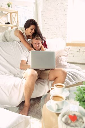 Couple of lovers at home relaxing together. Caucasian man and woman having weekend, looks tender and happy. Concept of relations, family, autumn and winter comfort. Watching cinema and laughting.