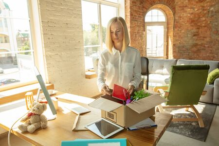 Young businesswoman fired, looks upset. Has to pack her office belongings and to leave work place for new worker. Problems in occupation, stress, unemployment, new way of life or end of career. Stockfoto