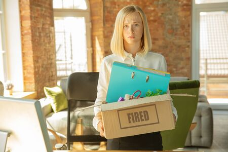 Young businesswoman fired, looks upset. Has to pack her office belongings and to leave work place for new worker. Problems in occupation, stress, unemployment, new way of life or end of career. 写真素材