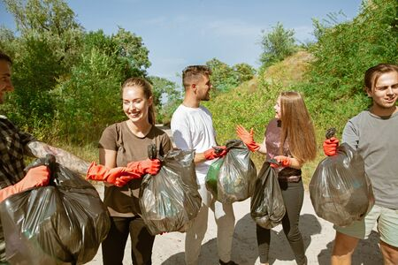 Team of building the future. Group of volunteers tidying up rubbish on beach in sunny day. Young men and women take care of nature and environment, taking bottles and packs away. Concept of ecology.