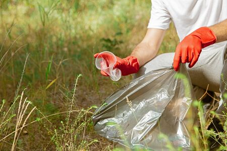 Build healthy home together. Group of volunteers tidying up rubbish on beach in sunny day. Young man take care of nature and environment, taking bottles and packs away. Concept of ecology. Stockfoto