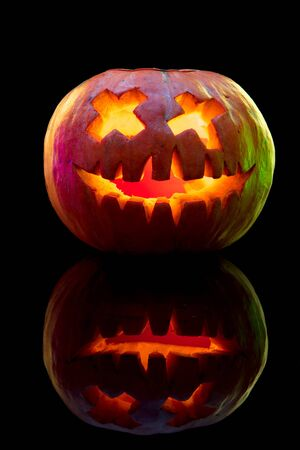 Halloween pumpkin head jack-o-lantern with scary evil face. Seasonal illuminated decoration. Looks scary, colorful neon light and dark background. Holidays. Black friday, sales. Night of fear. Stock Photo