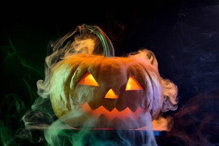 Halloween pumpkin head jack-o-lantern with scary evil face. Seasonal illuminated decoration. Looks scary, neon light, white smoke and dark background. Holidays. Black friday, sales. Night of fear. Stock Photo