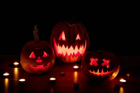 Halloween pumpkin head jack-o-lantern with scary evil faces and candles. Seasonal illuminated decoration. Looks scary, colorful neon light and dark background. Holidays. Black friday, sales.