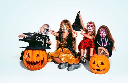 Kids or teens like witches and vampires with bones and pumpkin on white background. Caucasian models looks scary and playful. Halloween, black friday, sales, autumn holidays concept. The night of fear.