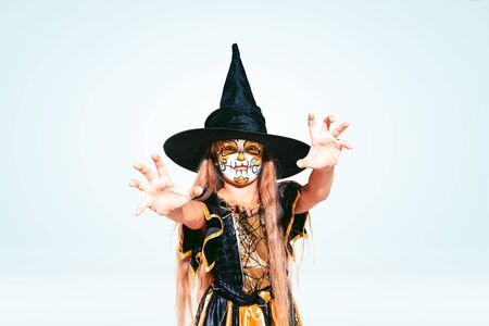 Little girl like a witch in scary yellow-black costume with glitter on white background. Caucasian female model looks scary. Halloween, black friday, sales, autumn holidays concept. The night of fear.
