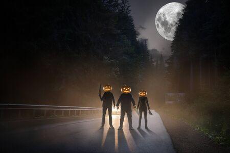 Tema di Halloween: maniaci spaventosi con testa di zucca sulla strada sullo sfondo del cielo con la luna di mezzanotte nel faro dell'auto. Fai attenzione mentre torni a casa alla fine di ottobre. Orribile concetto di fantasia. Archivio Fotografico