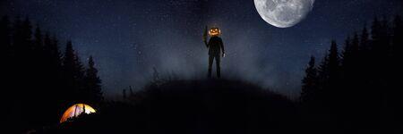 Tema de Halloween: maníaco aterrador con cabeza de calabaza en el bosque oscuro sobre fondo de cielo con luna de medianoche. La gente de camping no sabe cuál es el peligro. Fantasía horrible. Octubre, concepto de terror. Foto de archivo
