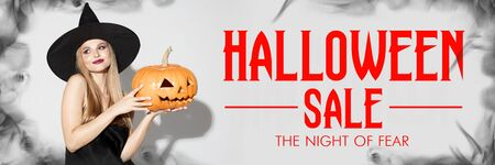 Young blonde woman in black hat on scary white background. Attractive caucasian female model smiling. Halloween sales, black friday, cyber monday, autumn concept. Flyer for your ad. Holding pumpkin.