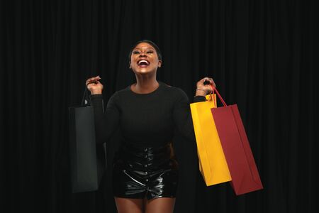 Young african-american woman shopping with colorful packs on black background. Attractive female model. Finance, black friday, cyber monday, sales, autumn concept. Copyspace. Smiling, crazy happy. Stock Photo