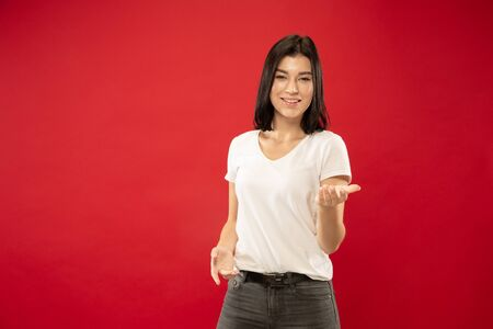 Caucasian young womans half-length portrait on red studio background. Beautiful female model in white shirt. Concept of human emotions, facial expression. Showing something, inviting, choosing.