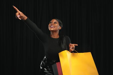 Young african-american woman shopping with colorful packs on black background. Attractive female model. Finance, black friday, cyber monday, sales, autumn concept. Copyspace. Smiling, pointing happy.