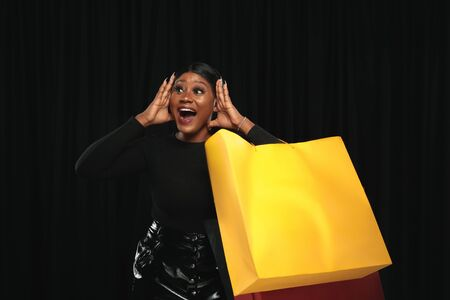 Young african-american woman shopping with colorful packs on black background. Attractive female model. Finance, black friday, cyber monday, sales, autumn concept. Copyspace. Smiling, screaming happy. Stock Photo