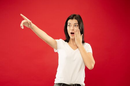Caucasian young womans half-length portrait on red studio background. Beautiful female model in white shirt. Concept of human emotions, facial expression. Pointing something, shocked, astonished.