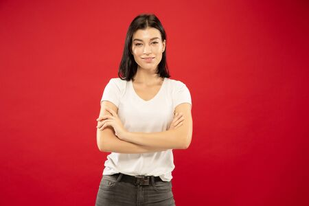 Caucasian young womans half-length portrait on red studio background. Beautiful female model in white shirt. Concept of human emotions, facial expression. Standing with hands crossed and smiling,