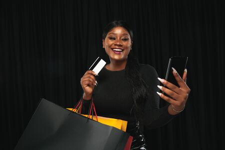 Young african-american woman shopping with colorful packs on black background. Attractive female model. Finance, black friday, cyber monday, sales, autumn concept. Copyspace. Online payment bill. Stock Photo