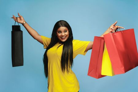 Young african-american woman shopping with colorful packs on blue background. Attractive female model. Finance, black friday, cyber monday, sales, autumn concept. Copyspace. Happy showing purchases.