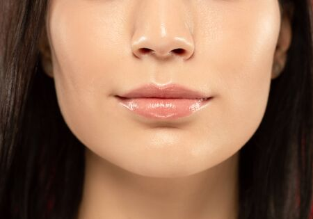 Beautiful young womans full lips close-up shot. Female model with well-kept skin and hair. Perfect skincare, human emotions, facial expression, beauty and cosmetics concept. Looks calm.