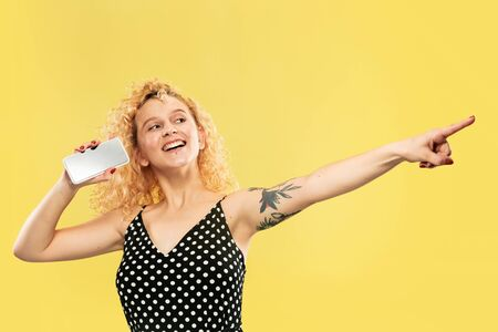 Caucasian young womans half-length portrait on yellow studio background. Beautiful female model in black dress. Concept of human emotions, facial expression. Showing phones screen, looks crazy happy.