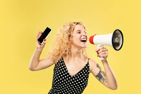 Caucasian young womans half-length portrait on yellow studio background. Beautiful model in dress. Concept of human emotions, facial expression, sales. Showing phones screen, calling with mouthpeace.