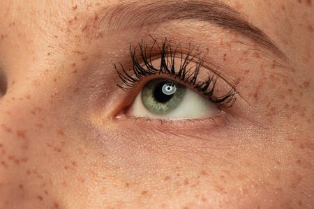 Beautiful young womans eye close-up shot. Female model with well-kept skin. Perfect skincare, human emotions, facial expression, beauty and cosmetics concept. Deep green color and eyebrows.