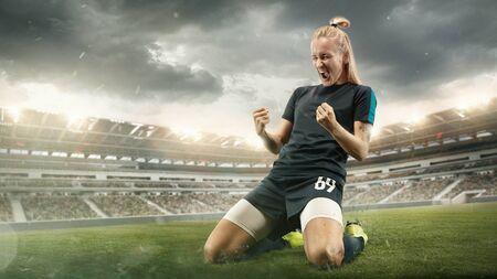 Proef of win. Jonge vrouwelijke voetbal- of voetballer in sportkleding die het doel in actie viert in het stadion tijdens het spelen. Concept van gezonde levensstijl, professionele sport, hobby, beweging, beweging.