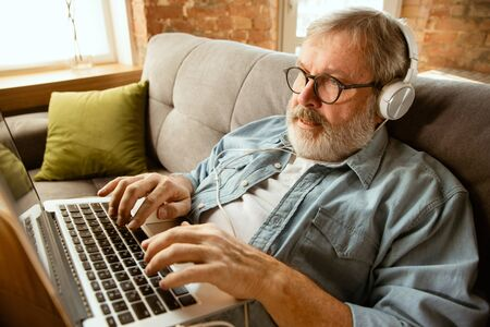 Senior man working with laptop at home - concept of home studying. Caucasian male model sitting on sofa and doing his homework or serfing in internet, watching cinema or webinar, playing games.