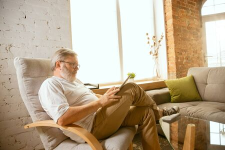 Senior man working with tablet at home - concept of home studying. Caucasian male model sitting on sofa and doing his homework serfing in internet, watching cinema or webinar, online lessons. Stock Photo